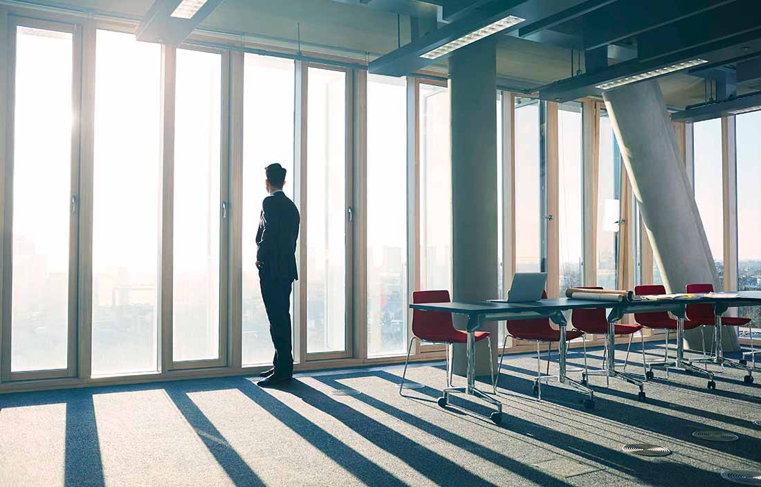 Businessman standing in his office looking out the window.