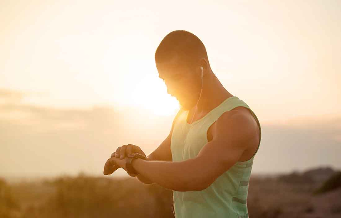 Man in workout gear checking is smart watch fitness device.