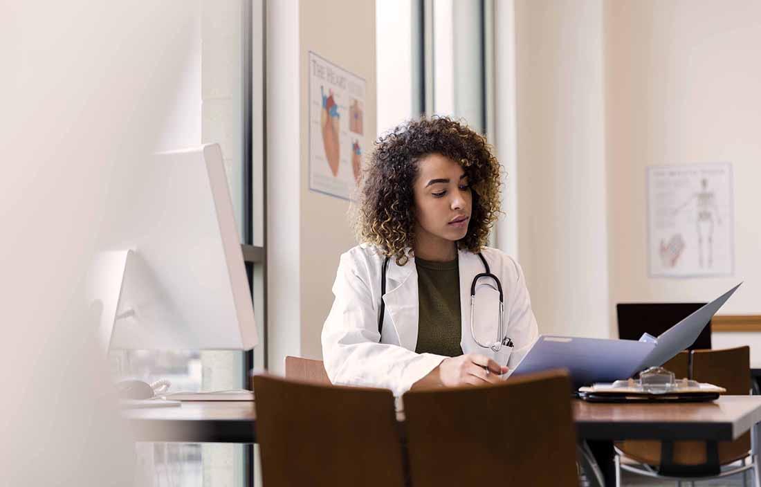 Healthcare worker sitting at a table, reading files