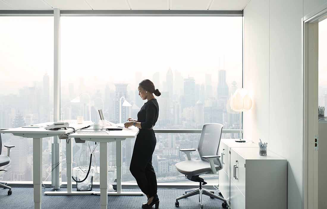 Woman in a glass office standing at a desk with a laptop