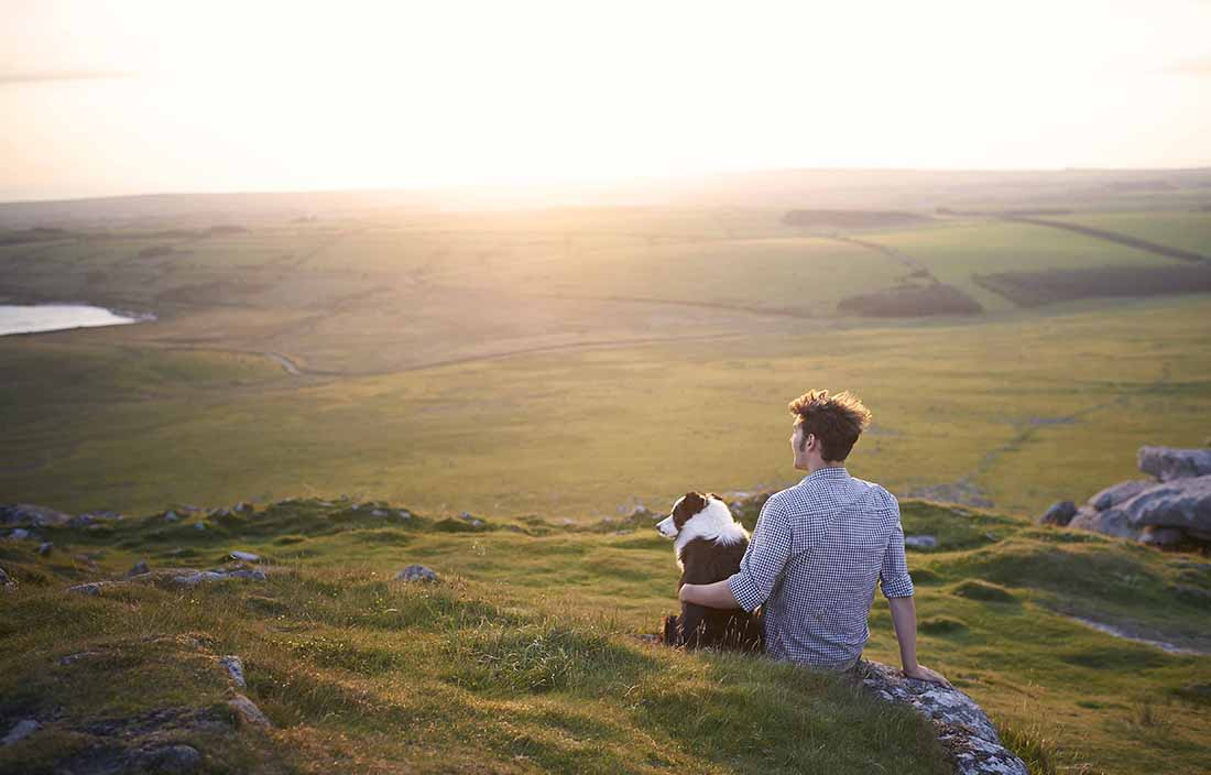 A man sitting on a grassy hill with his dog