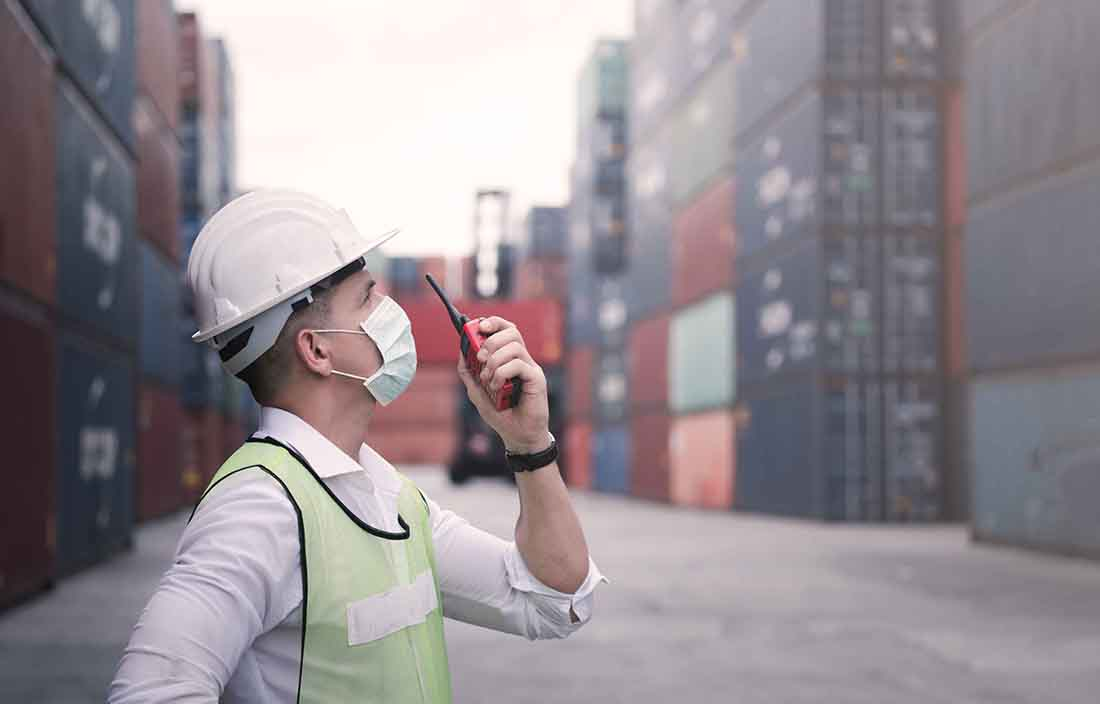 Worker in a hard hat, wearing a mask, talking into a walkie talkie