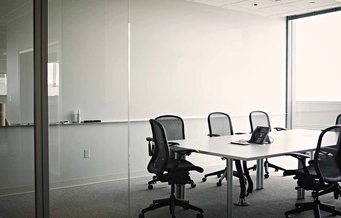 An empty conference room with chairs lining a conference table.