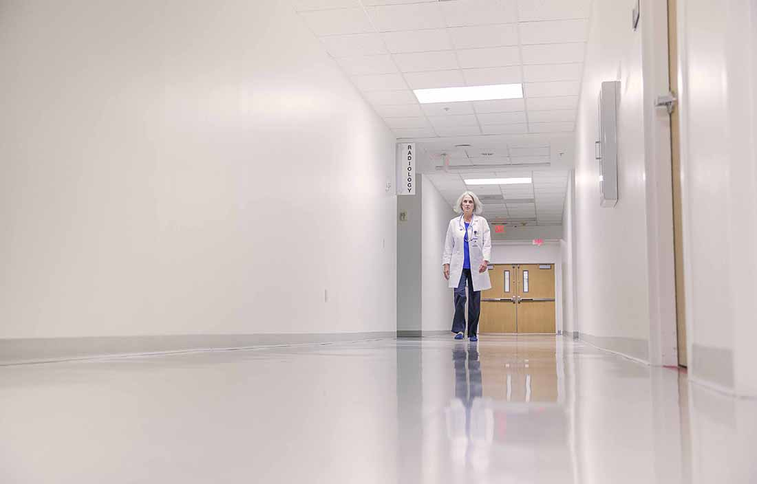 Healthcare worker walking down a hospital hallway