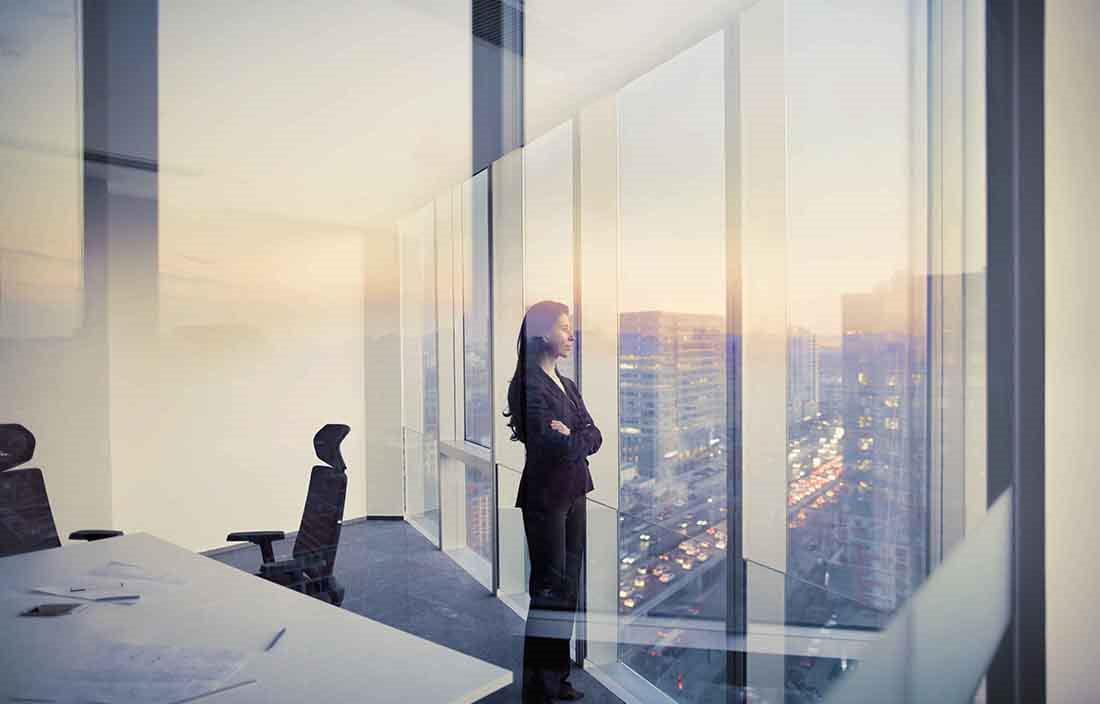 Woman standing in office looking out the window at the city skyline.