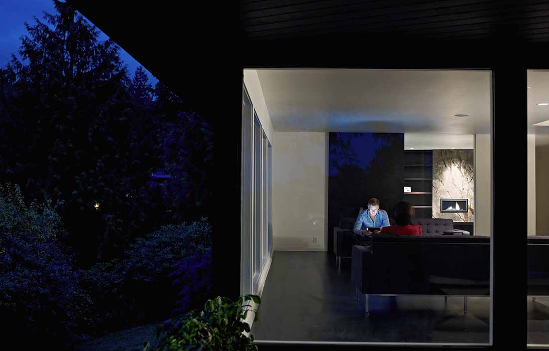 Man sitting in a darken living room on his tablet