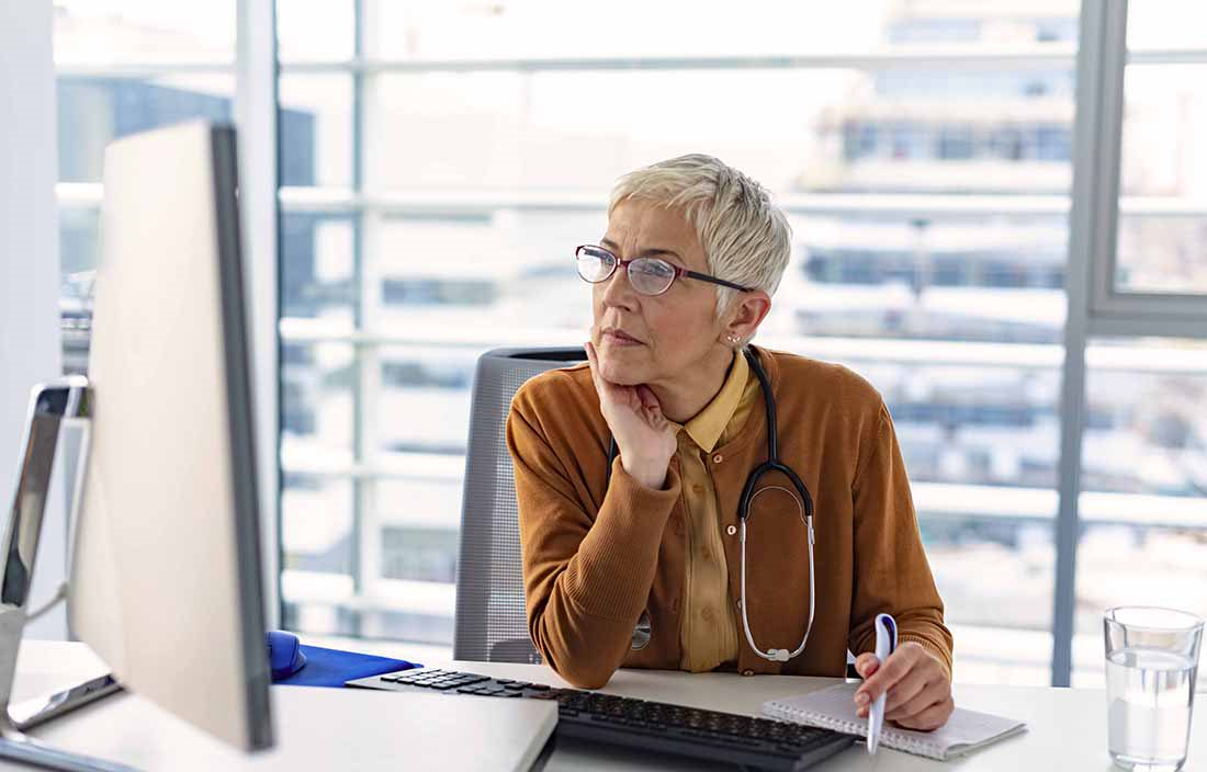 Elderly woman wearing a stethoscope while using a desktop computer.