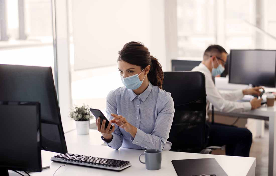 Woman wearing a mask while sitting at her desk, typing on her cellphone