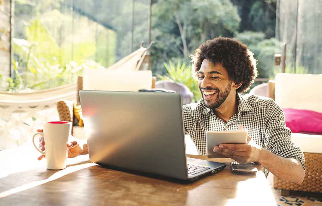 Man working from home smiling and laughing while using a laptop computer.