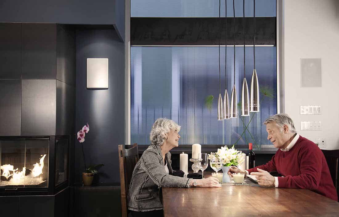 Elderly couple sitting at a dinner table talking.