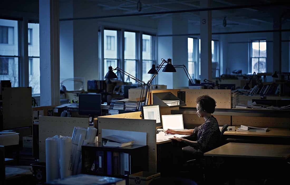 Woman sitting in a dark office on her computer