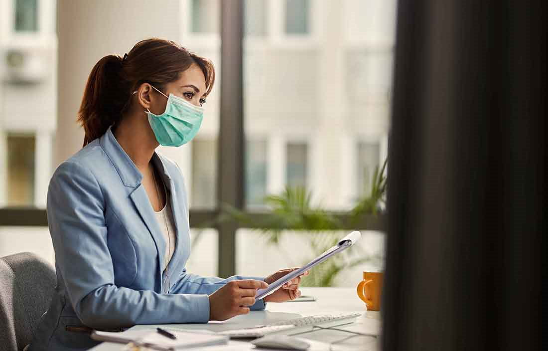Businesswoman sitting at desk wearing a protective facemask while reviewing a notepad.