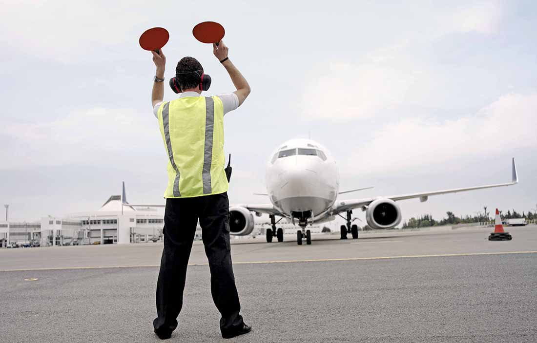Runway worker at an airport guiding a plan for landing.