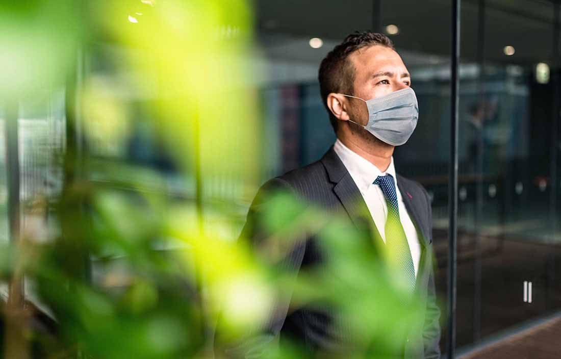 Man in a suit and wearing a mask standing next to a window