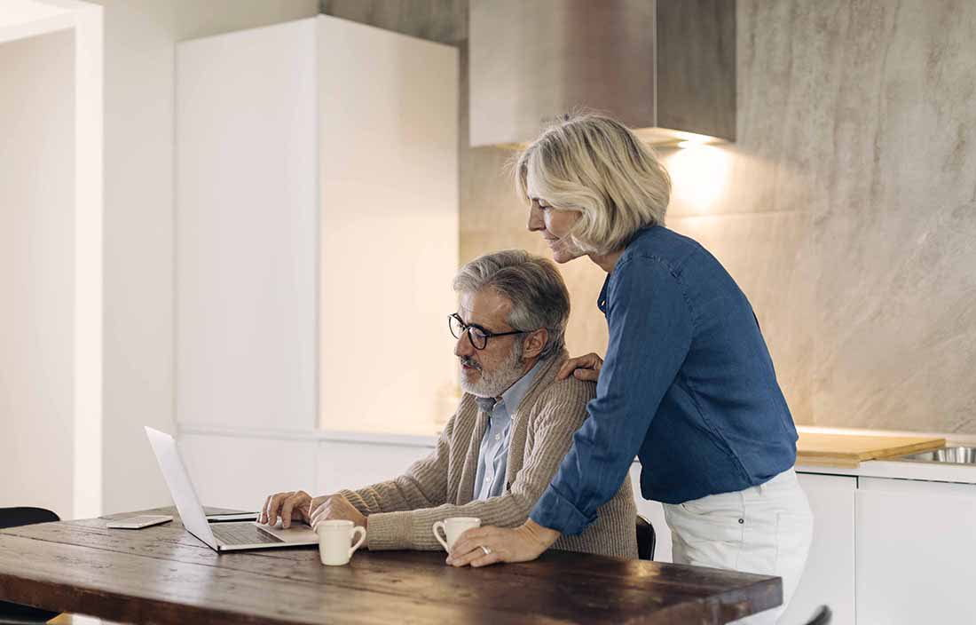 Elderly couple in the kitchen using a laptop computer while drinking coffee.