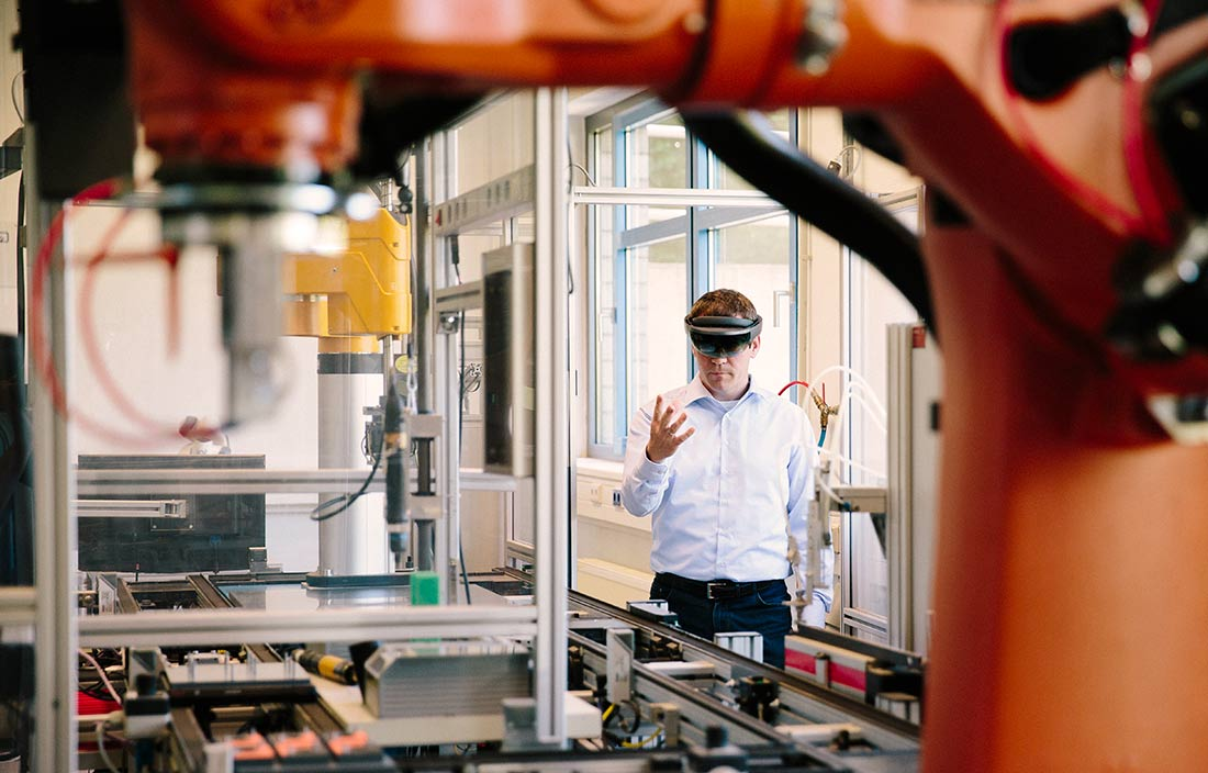 Businessman in a factory workshop wearing VR goggles and holding hands up.
