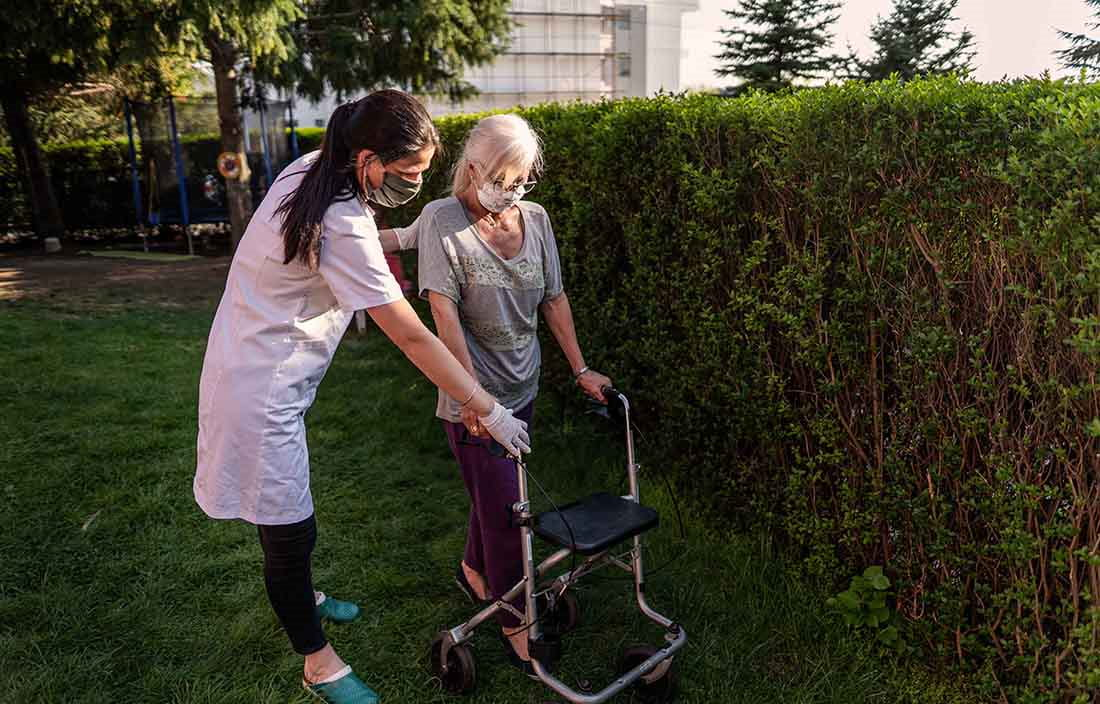 Nurse helping a elderly woman use her assisted walking device in an outdoor area.