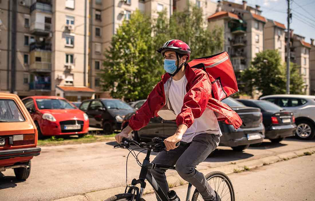 Delivery worker riding a bike while wearing a protective facemask.