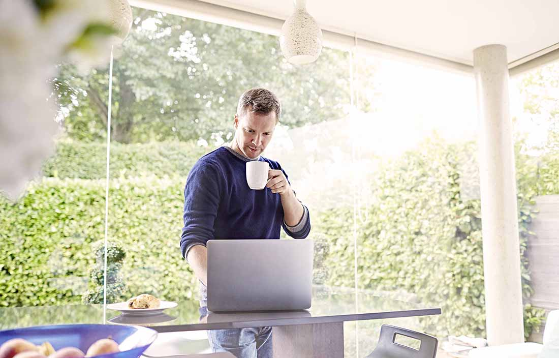 Man using laptop computer in kitchen while standing drinking a cup of coffee.