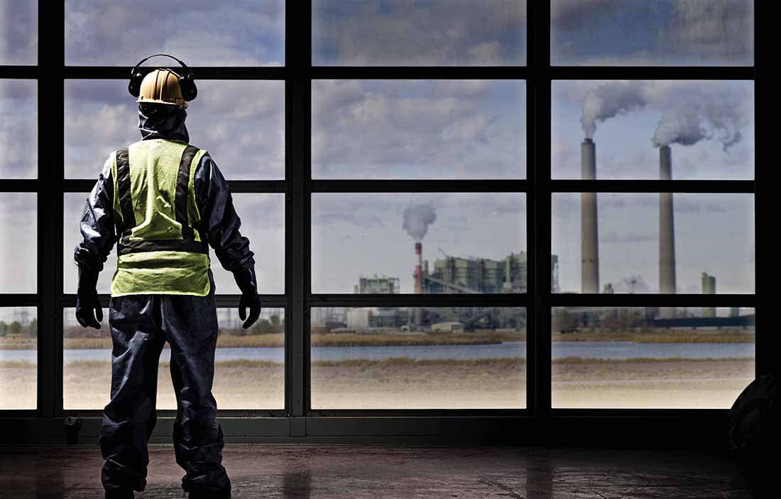 Construction worker looking out a window towards an industrial factory site.