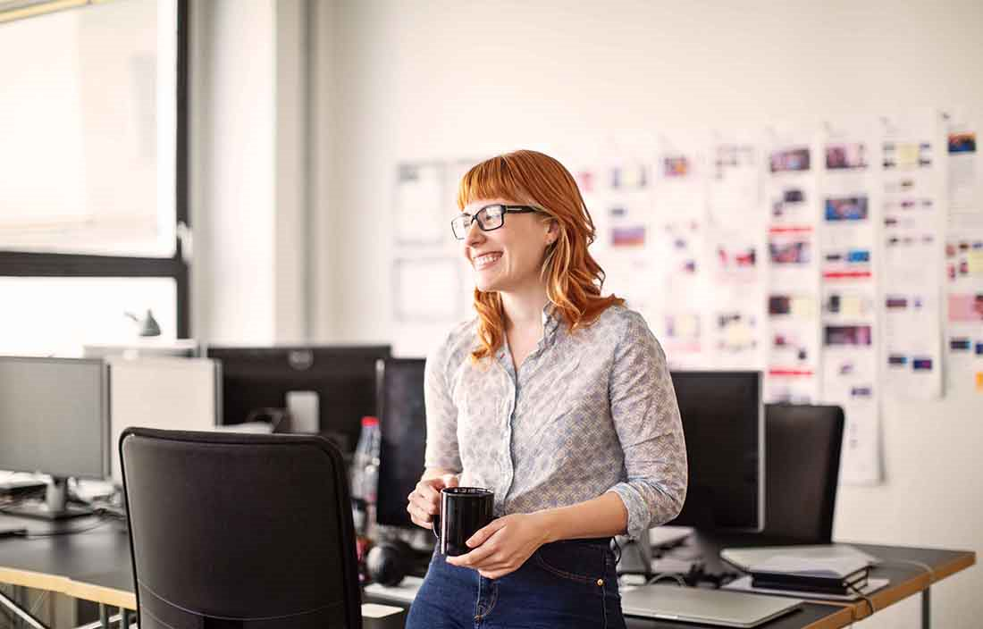 Red haired businesswoman smiling in the office holding a cup of coffee.