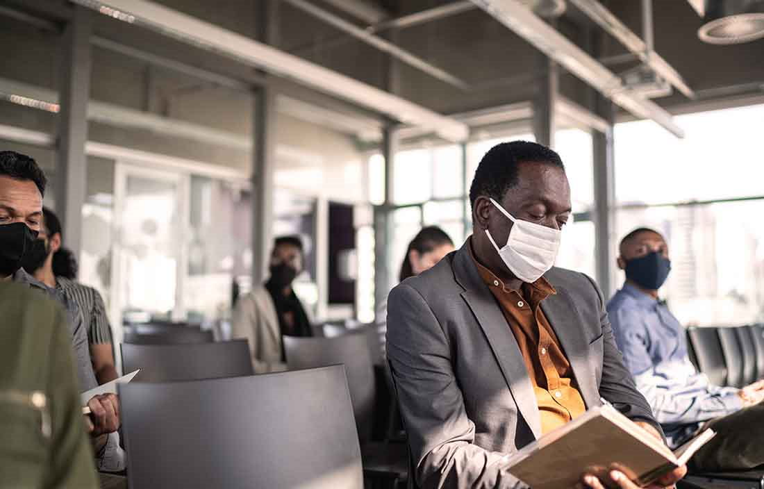 A group of business people in a waiting area wearing protective face masks for COVID-19.
