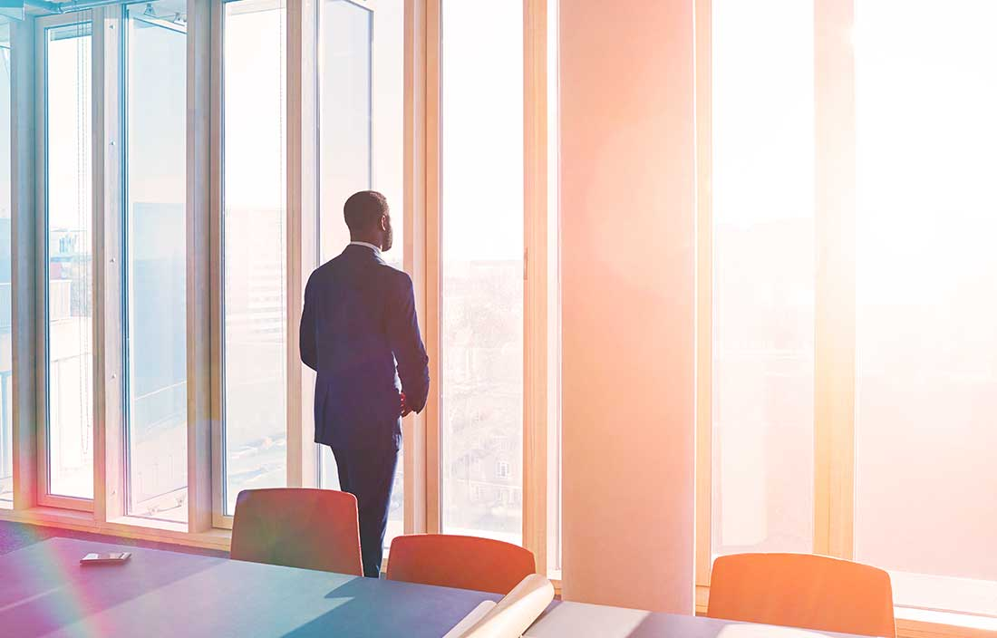 Businessman standing in a sunny conference room looking out the windows.