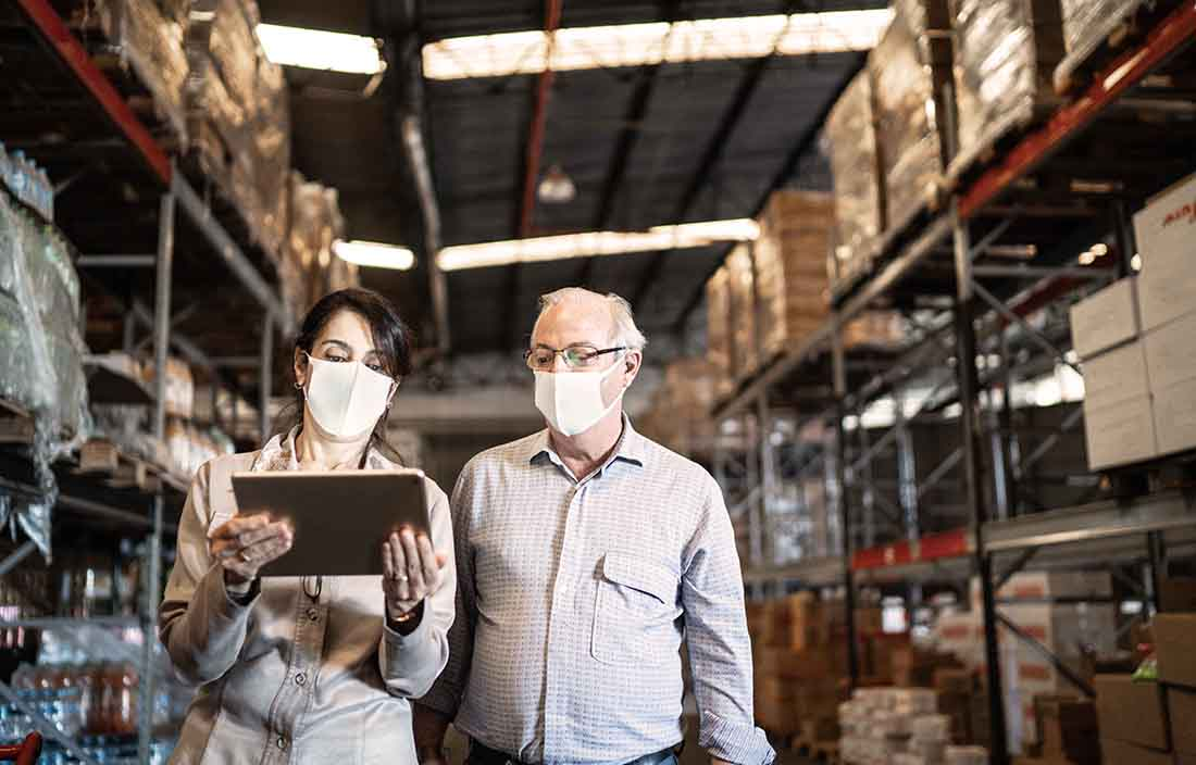 Two businesspeople walking through a warehouse reviewing levels of supply.
