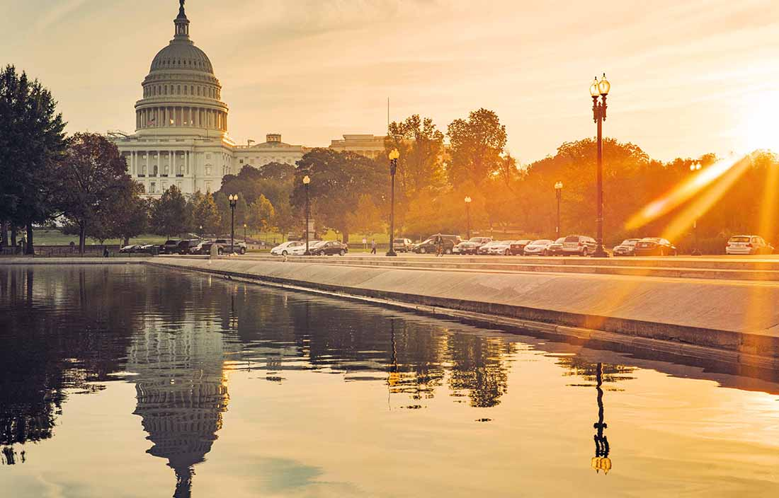 View of the United States Capitol building at dawn with the sun setting.