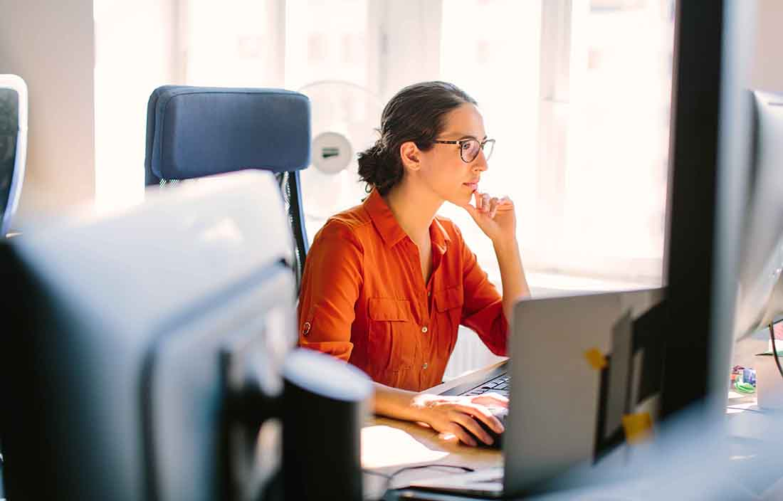 Businesswoman sitting at her desk looking at a computer monitor.