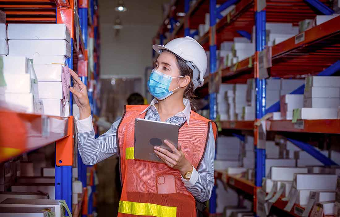 Automotive worker in protective gear checking inventory levels in warehouse.