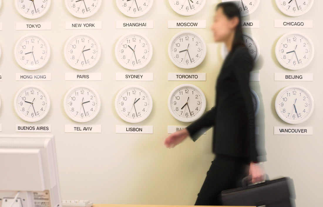 Japanese business woman walking past a wall with international clocks.