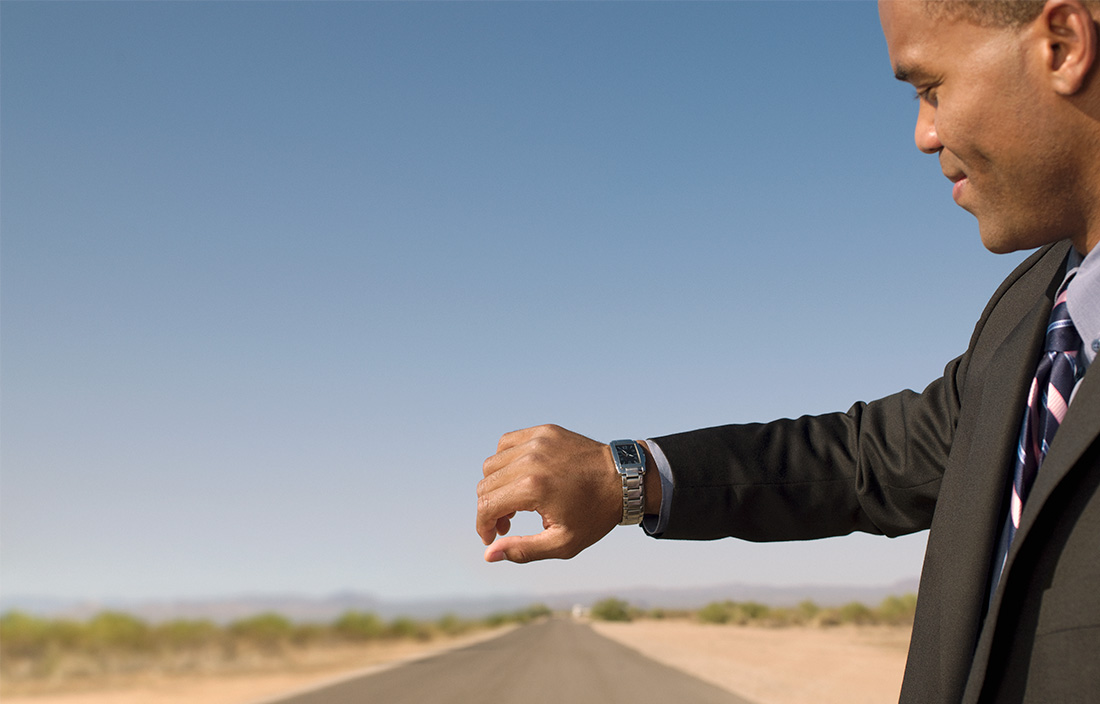 A man checking and looking at his watch on a desert road.