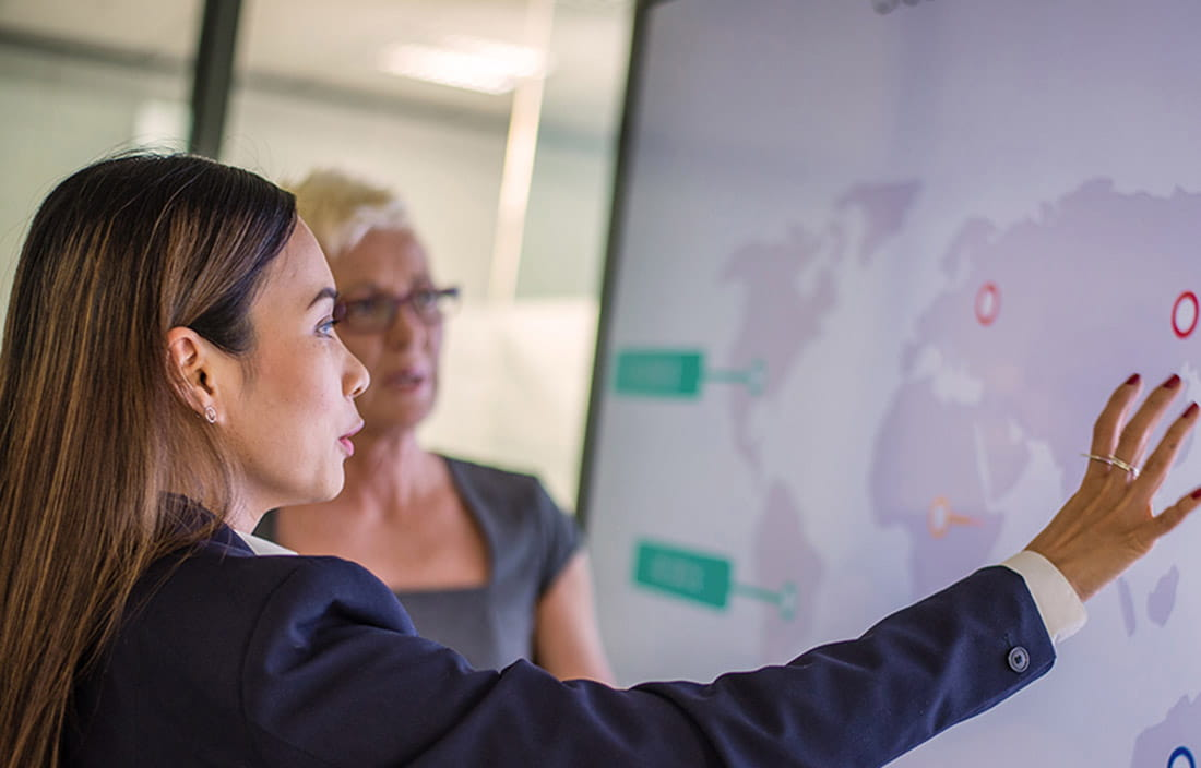 Two female business colleagues analyzing business locations on a global map