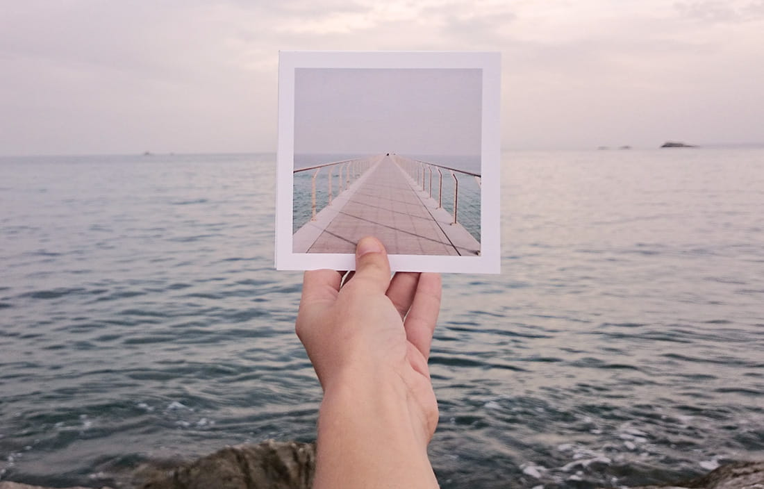 Image of hand holding picture of dock against a background of water