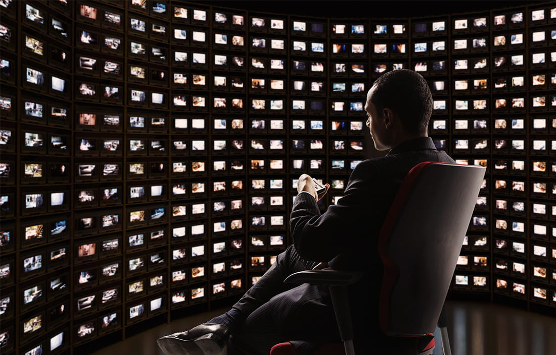 Image of man sitting in front of many different screens