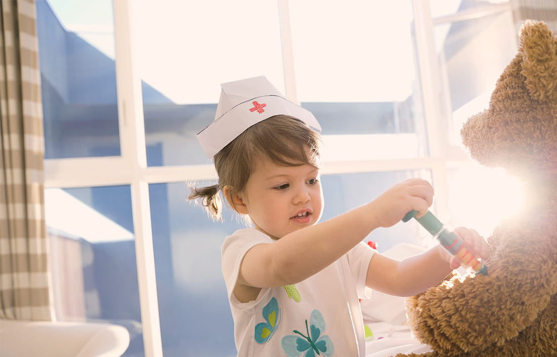 Image of toddler playing doctor with a teddy bear