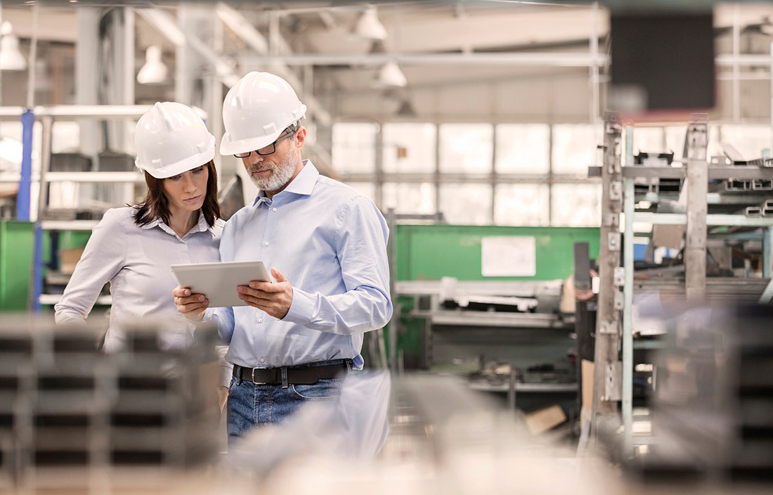 A man and woman standing in a factory wearing hard hats and reading an iPad