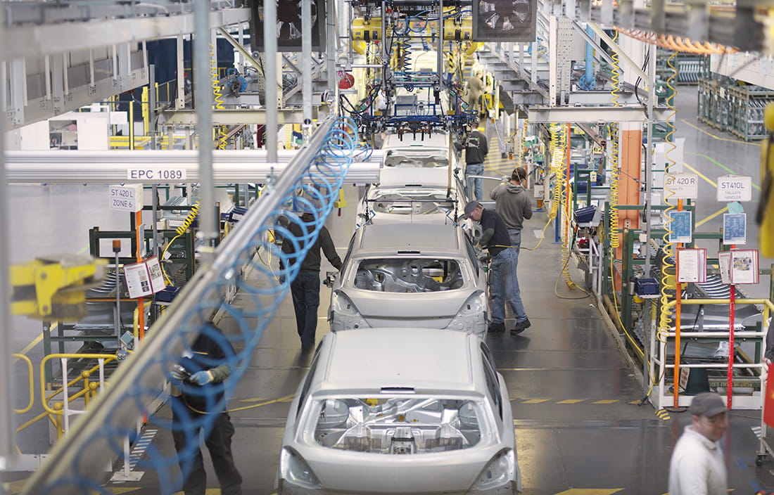 Automotive workers inside a factory building cars