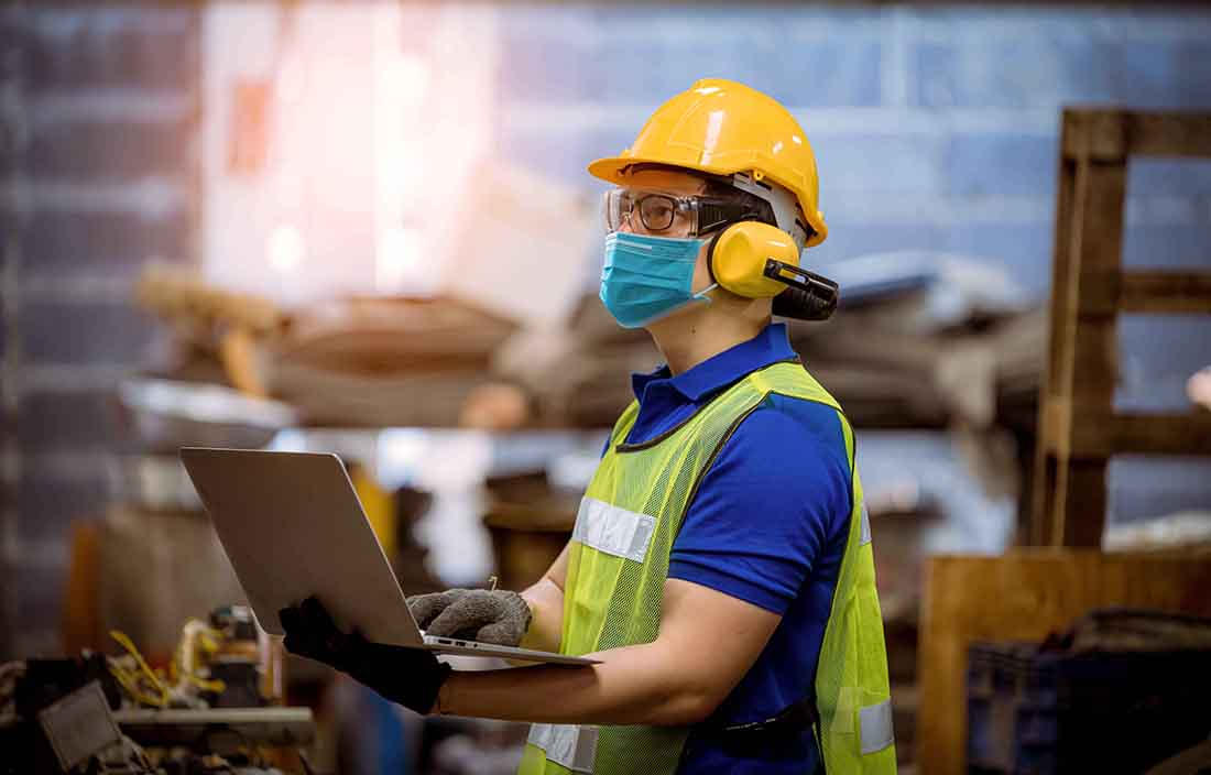 Factory worker in a mask on a laptop