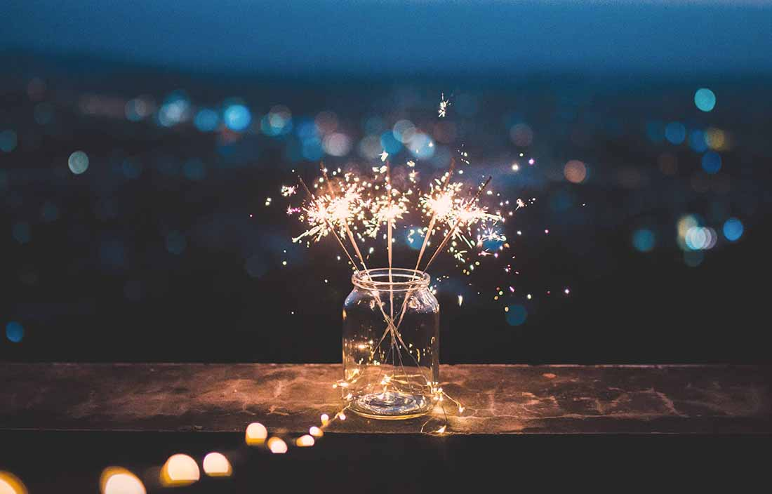 Close up photo of sparkler fireworks going off inside of a glass jar.