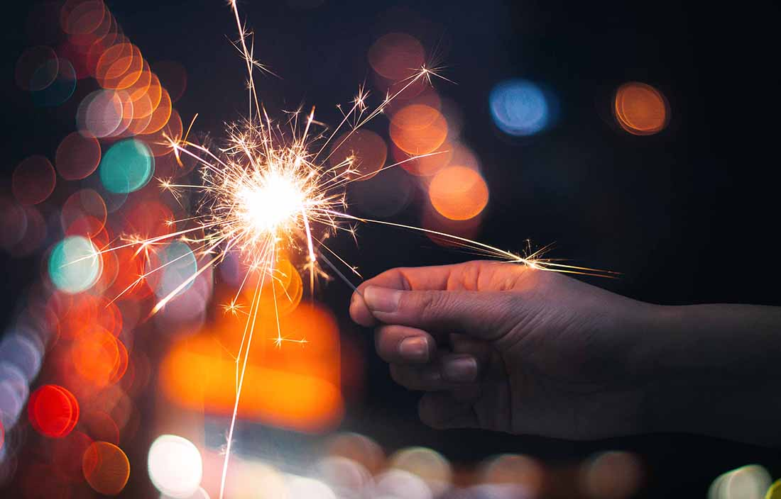 A hand holding a sparkler