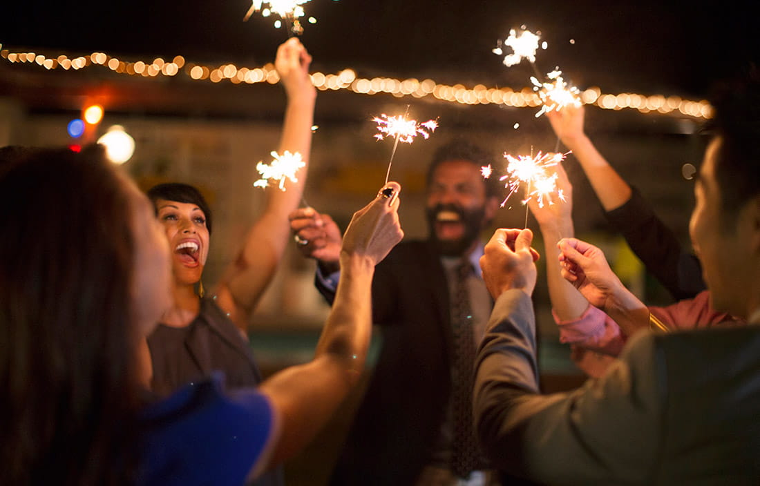People excitedly celebrating with sparklers at night.