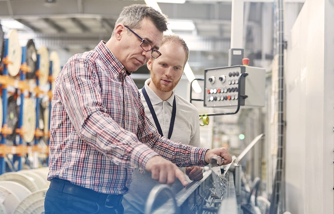 Image of two men in a manufacturing facility look at a piece of equipment.