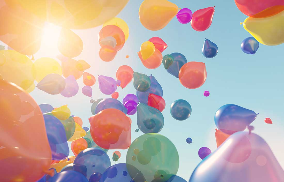 Colorful balloons rising up loose into the air on a sunny, clear sky