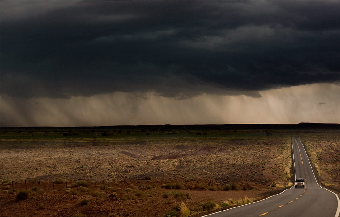 Image of car driving on a desert road heading away from a storm
