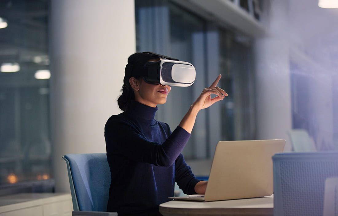 Professional woman using virtual reality glasses and a laptop