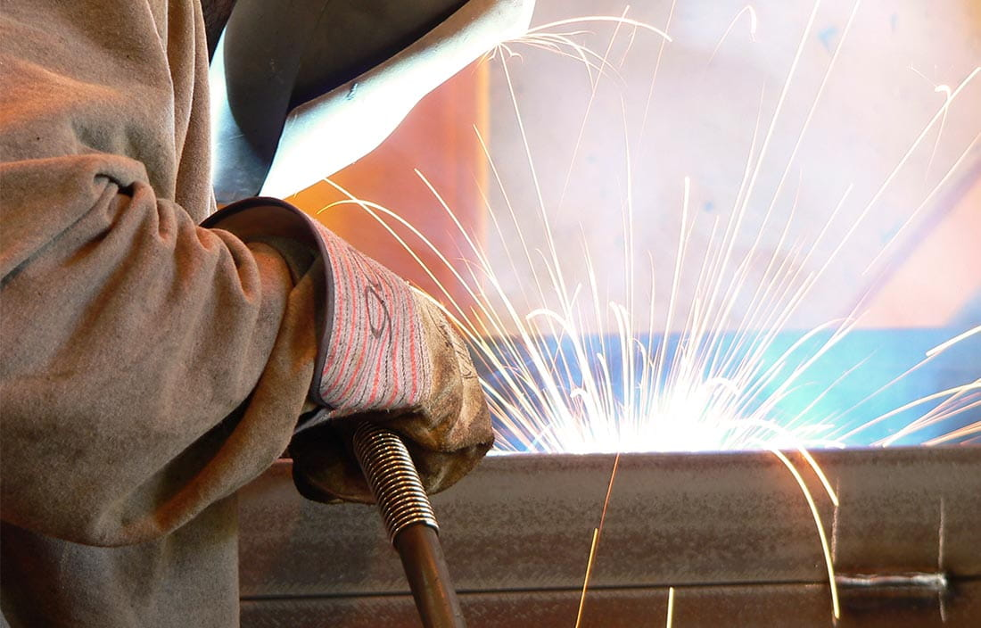Image of welder welding a steel beam