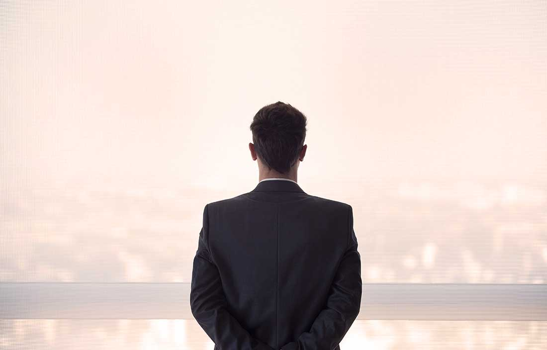 Executive, male and fairly young, looking out a window over real estate with his back toward the viewer