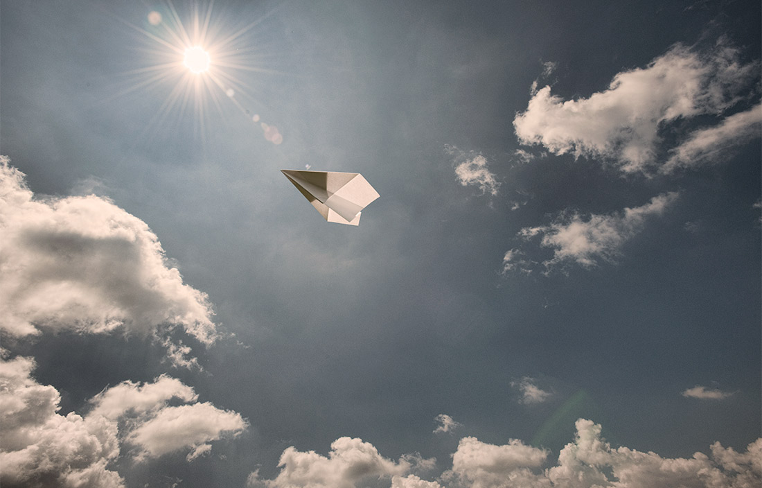 paper airplane flying high in a sunny sky